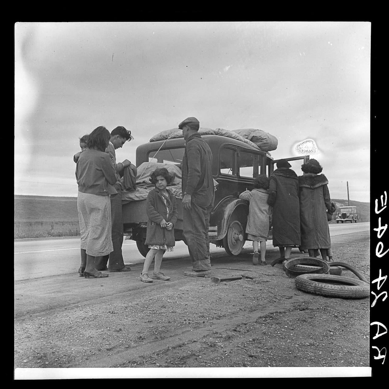 Dorothea Lange, <em>Migrants, family of Mexicans, on road with tire trouble. Looking for work in the peas. California.</em>